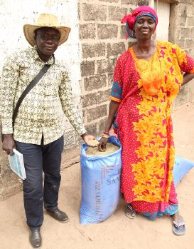 Thiane shows off a bag of bio-fortified millet that she grew with support from SPRING Agriculture Advisor, Aliou Babou.