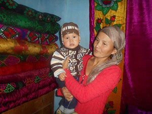 Rural mother Seitova Raima and her eight-month-old son benefitted from USAID-supported trainings in infant and young child feeding practices.