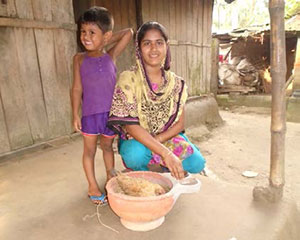 In Durgapur village, a farmer nutrition school graduate and her son tend to the chickens that produce important nutrients for their family.