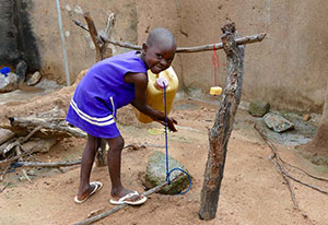 A young child grins at the camera as he washes his hands at a tippy tap.