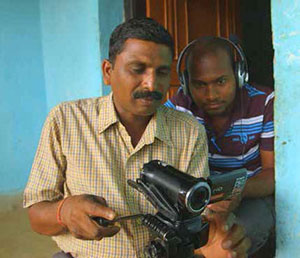 Two men sit together, one behind the other. The man in front holds a video camera and looks at it intensely. The man behind looks wears headphones and has a laptop in his lap. He looks over the first man's shoulder at the camera.