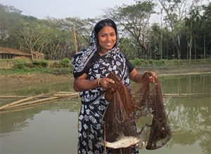 Photo of a woman holding a fishing net in a pond