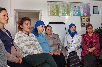 A group of six Kyrgyz women sits in a line of chairs. They are listening, but bored.
