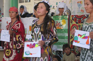 Photo of women speaking and holding diagrams and paintings of bowls of fruit.
