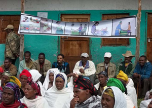 Photo of several people seated outside listening under a banner with medical illustrations.