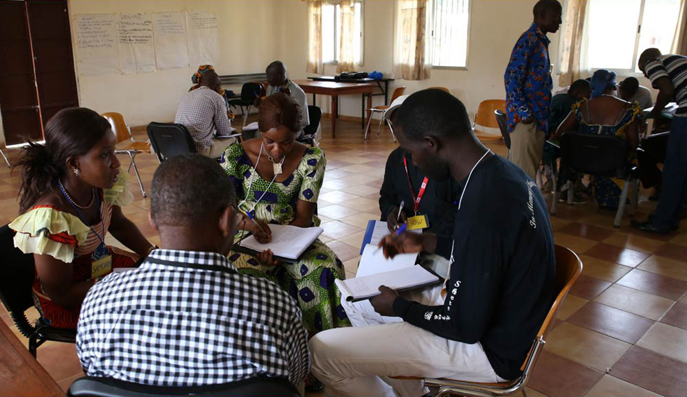 Photo of people gathered in classroom groups adapting pops storyboards in Guinea