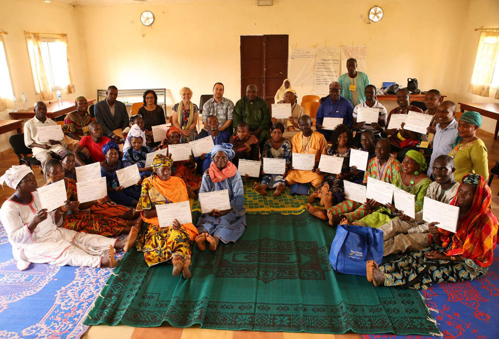 Photo of a room of people receiving MIYCN training certificates in Guinea