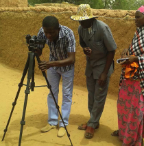 Photo of three people working a video camera on a tripod