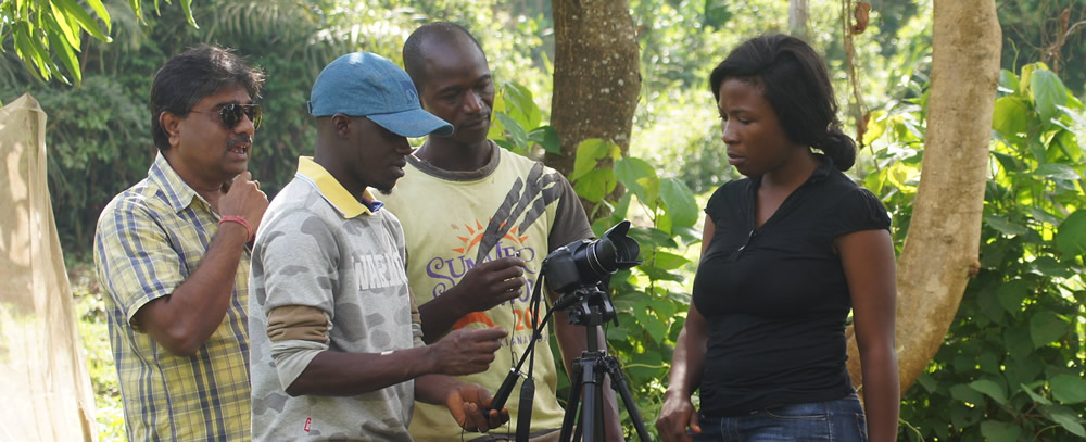 Group of people setting up a camera with a forest in the background.