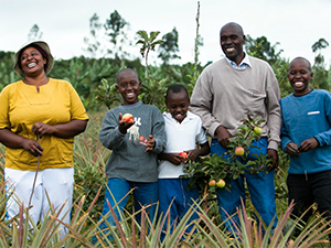 Photo of adults and children holding produce and smiling. USAID/Morgana Wingard