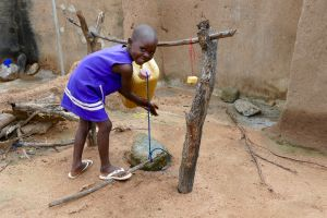 A young girl uses a tippy-tap to wash her hands.