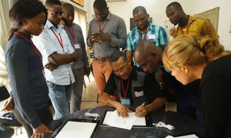 Participants look on as lead trainer Victor Nolasco demonstrates line drawing using a light table.