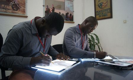Shekuba Kandeh of HKI Sierra Leone and Ahmed Mansaray of the Sierra Leone Agriculture Research Institute practice line drawings on two light tables.