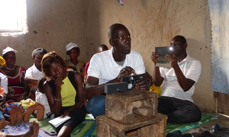 A SPRING/Guinea volunteer community worker sets-up a Pico projector to show the community video. SPRING/Guinea has developed community videos featuring exclusive breastfeeding practices, child nutrition, dietary diversity, handwashing with soap, benefits of consuming legumes, and processing potato leaves for off-season consumption.