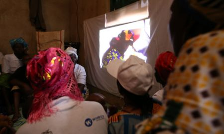 Community members in Beindou watch a local community video.