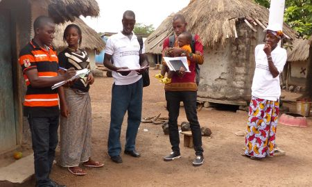 A SPRING/Guinea community volunteer in Bieindou demonstrates a home visit to the Sierra Leone visitors. Home visits reinforce messages promoted during the community video and assesses the family's understanding of these key messages.