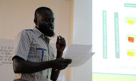 Peace Corps agriculture trainer, Maharmeth, presents his group's case study on the agricultural income pathway.