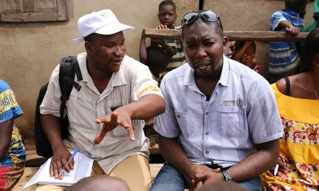 A SPRING/Guinea community extension agent who supports the COCO data collection explains his role to Hamid Turay, SPRING/Sierra Leone Nutrition Coordinator.