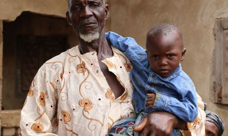 A grandfather poses with his grandchild. Grandfathers are key influencers of household behaviors. SPRING is committed to engaging grandfathers and other key influencers like mothers-in-law and community leaders in community video dissemination events.