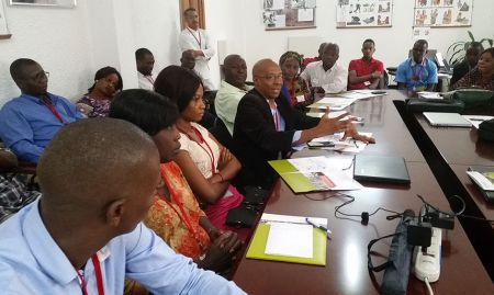 "Leaders of local artists' cooperative ""Bulle d'encre"" (""Ink Bubble"") Youssouf Ben Barry Oscar and Aïssatou Kâdè Balde and participants in the photo-to-illustration workshop explain to partners how to contact the cooperative to take advantage of photo-to-illustration services now being offered in Conakry."