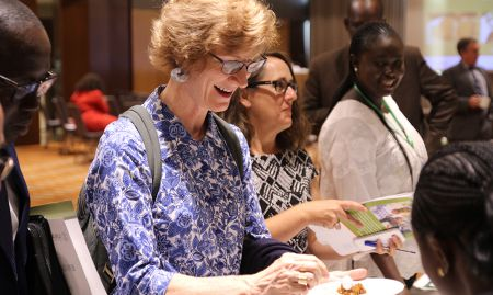 USAID Senegal Mission director Lisa Franchett tastes a meal made from the nutritious crops that SPRING/ Senegal promoted.