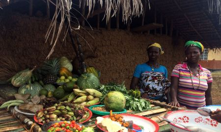 A community women's group presents produce that they grew in their community garden, supported by a local NGO.
