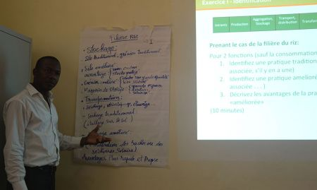 A staff participant explains his group's ideas about the advantages of improved technologies within the rice value chain.