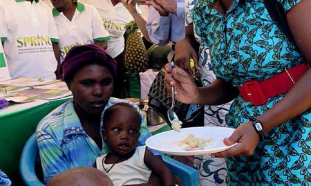 Guest of Honor Dr. Jacent Assimwe demonstrates how to feed a child with the food mixed with MNPs