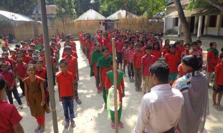 Children standing in lines in front of tippy taps