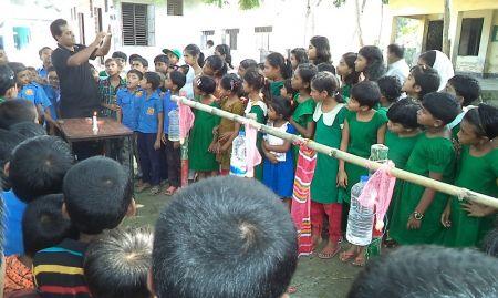 Group of children watching a man give a handwashing demonstration