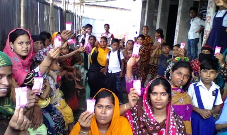 Group of women and children holding up packages of soap