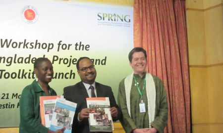 Dr. Altrena Mukuria and Dr. Iftekhar Rashid show the Farmer Nutrition School toolkit materials in English and Bangla at the Launching of the toolkit.