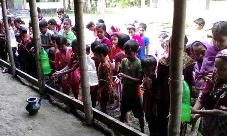 Women and children using tippy taps