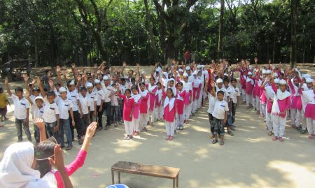 Several lines of children with hands up responding to their teacher