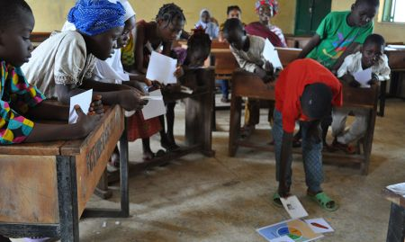 Children aged 6-11 practice categorizing healthy foods during concept testing for nutrition and hygiene activities included in a training package geared towards OVCs.