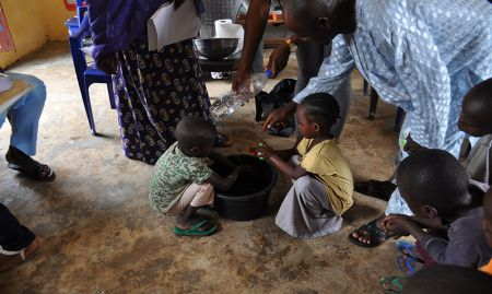 Children aged 2-5 practice handwashing with a tippy tap during concept testing for nutrition and hygiene activities included in a training package geared towards OVCs.