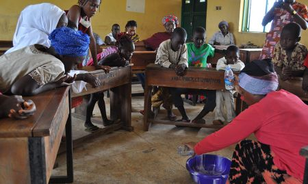 Children aged 6-11 watch a demonstration on meal frequency during concept testing for nutrition and hygiene activities included in a training package geared towards OVCs.