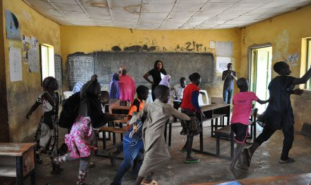 Children aged 6-11 play a game voting with their feet whether snacks are healthy or unhealthy during concept testing for nutrition and hygiene activities included in a training package geared towards OVCs.