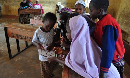 Adolescent girls aged 6-11 review an illustration on critical times to wash hands during concept testing for nutrition and hygiene activities included in a training package geared towards OVCs.