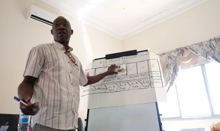 A participant, Ibrahima, shares his group's work on identifying a stage of the first 1000 days.