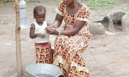 This community star demonstrates the proper handwashing procedure for herself and her child.