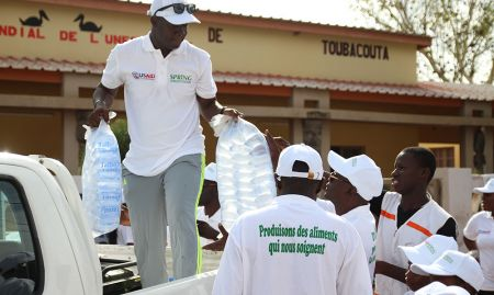 SPRING/Senegal SBCC Advisor Albert Boubane distributes water to participants before the hike.