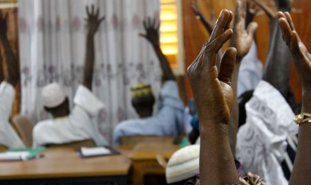 Participants raise their hands in agreement as part of a pre-training assessment on knowledge of gender concepts.