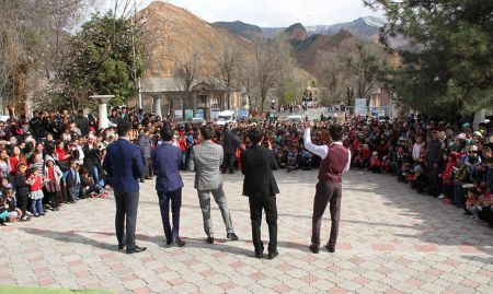 A singing group stands outside in a courtyard facing the large crowd wrapping around them.