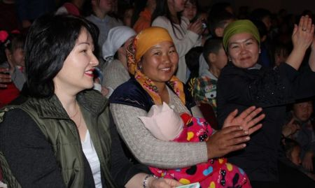 Three women and a baby clapping along.