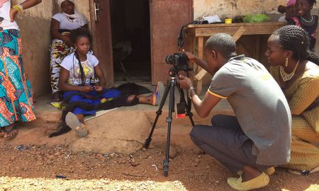 In April 2017, a new hub was formed in Mamou to serve partner projects in the central region of Guinea. These hubs were trained in the technical and creative processes of video production. Here, two training recipients, Millimouno and Jeannette, practice handling the video camera.