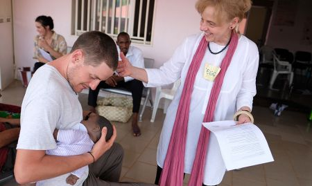 Peggy Koniz-Booher, SPRING SBCC Senior Advisor, guides the demonstration of proper breastfeeding with Peace Corps volunteer, George.