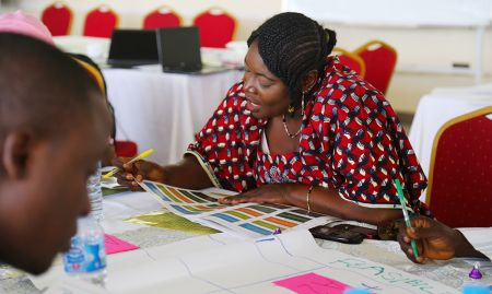 Participants like Ms. Maris S. Dangi, a Ward Focal Person from Kufana ward in Kajuru LGA, review a set of recommendations drafted by the study team.