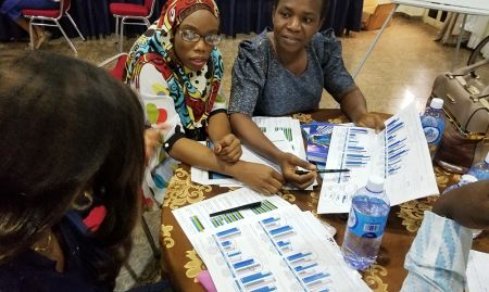 """In Abuja, participants analyze findings presented on """"data placemats""""."""