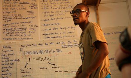 Peace Corps volunteer, DeVon, presents his group's seasonal calendar.
